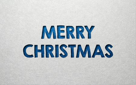 indent: Merry Christmas card or invitation design in textured blue indented text on a grey background with copy space for your seasonal greeting