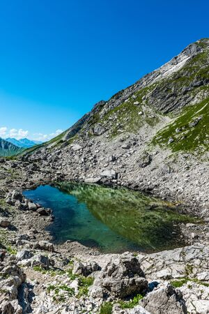 Reflective pool of water near rocky mountain summit during the summer in Allgau, Germany, Europe