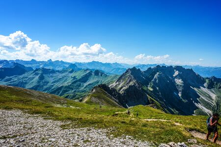 recedes: Single hiking sightseer at corner of grass and gravel covered mountain top in the Alps during summer Stock Photo