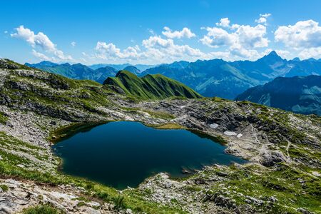 allgau: Beautiful calm little lake high up in the mountains reflecting blue sky in the Alps Stock Photo