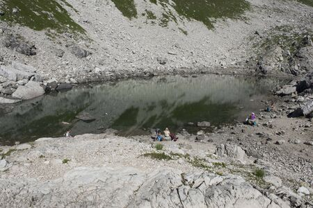 reflecting: Tiny lake or pool of water reflecting grass and rocks in mountain located in Germany