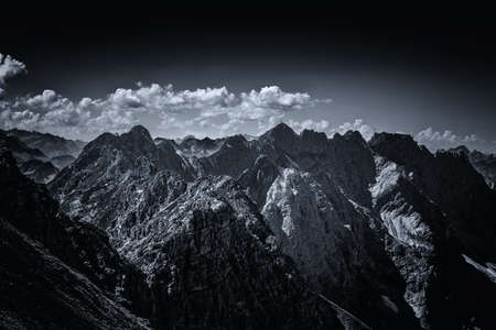 allgau: View on summit peaks from dark contrasty view on the Alps in Allgau Germany, Europe Stock Photo