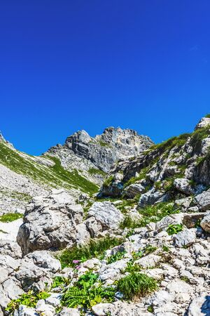View up toward mountain peak from rocky ground under deep blue sky in the Alps. Includes copy space.