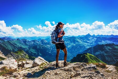 Rear view of fascinated female backpacker with long hair, shorts and poles looking across valley in the Alps