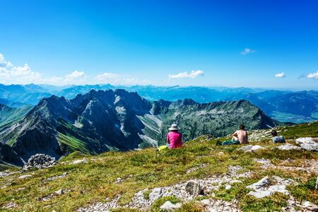 summits: Woman in hat sitting across from mountain top summit on grass and rock surface under blue sky with copy space