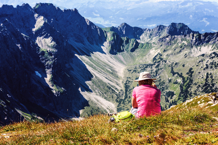 Back of hiker in pink sitting near edge of foothill facing large mountains of the Alps