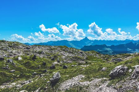 recedes: Rocks and boulders among green grass paths in the German Alps of Allgau during summer Stock Photo
