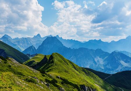 recedes: Grassy foothills in foreground of the Alps stretching beyond the distant horizon