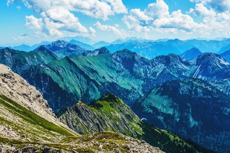 recedes: Green foothills of the Alps under beautiful blue skies with white clouds in Allgau Germany Stock Photo