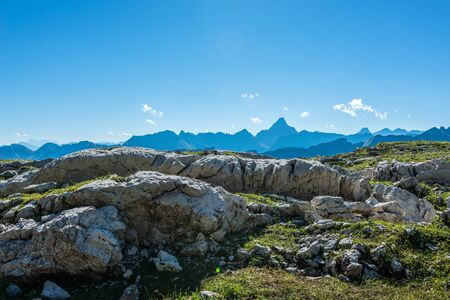 recedes: Old rock formations in foreground of the Grosser Daumen mountain range under clear blue sky