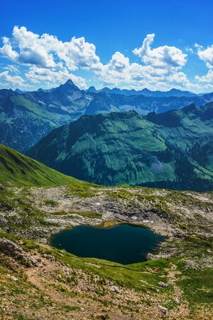 allgau: Rainwater pools in center of level mountain area surrounded by patches of grass with tall ranges nearby