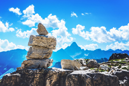 Rock cairn marking a hiking route in the Allgau alps on Grosser Daumen in Germany with a view to distant mountain peaks Stock Photo