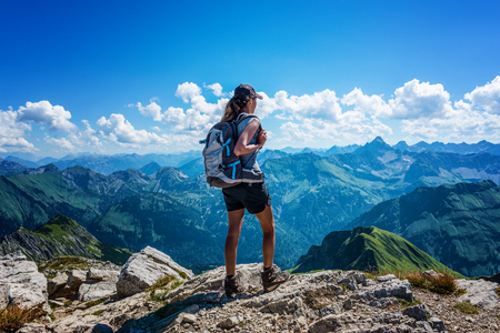 Single woman in hiking backpack and boots standing atop mountain looking over the German Alps Stock Photo