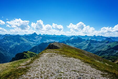 allgau: Gravel and grass covered hill facing the mountain scenery of the Alps in Germany