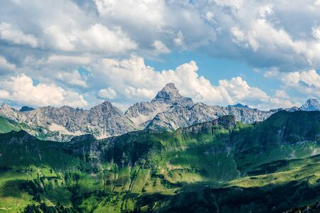 rugged terrain: Green small mountains in the foreground near the Alps under scattered clouds in Germany