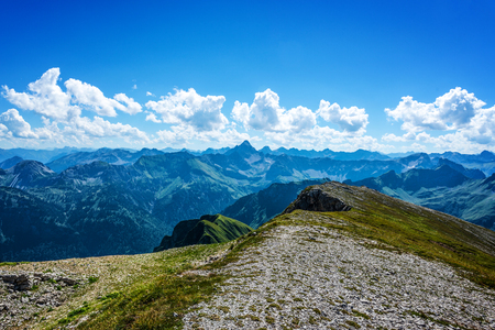 View of beautiful blue sky and white clouds above the Alps in Germany from grass and gravel covered summit