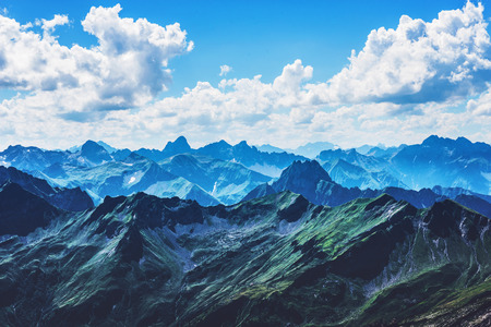 recedes: Sharp Alps mountain peaks under vast blue sky with white clouds in Allgau Germany