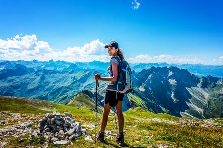 exteriores: Joven feliz en el equipo de senderismo mirando hacia atrás mientras se está ante la gran cordillera de los Alpes de Allgäu Foto de archivo