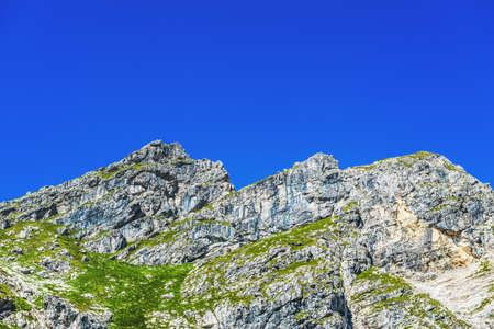 mountainside: View of rocky mountainside with patches of green grass from low angle. Includes copy space in sky. Stock Photo