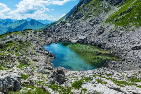 allgau: Scenic view of natural clear pool of water atop mountain with other tall ranges in the distance