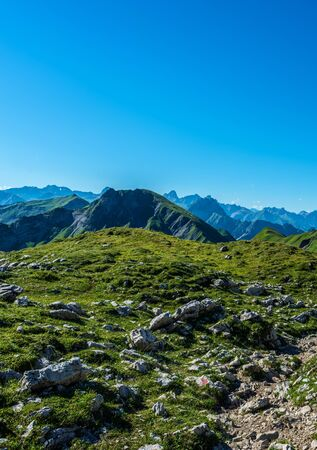 recedes: Old scattered rocks in grassy foothills of the Alps under deep blue sky with copy space