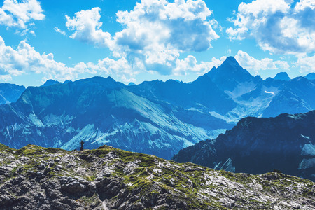 Crucifix in foreground of Alps mountaintop vista under scattered white clouds above Stock Photo