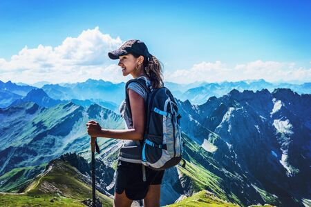 allgau: Attractive young woman trekking in the Allgau Alps on Grosser Daumen turning to watch something to the side with a smile against a backdrop of high rugged alpine mountains