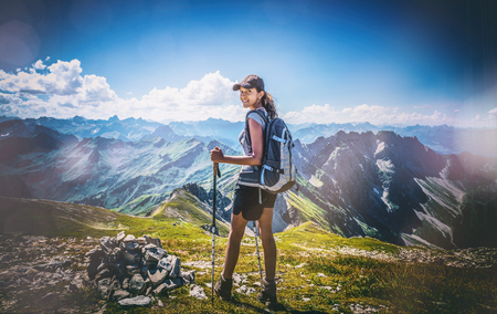 Toned image of an attractive young Indian woman backpacking in the Allgau Alps, Germany standing on an alpine plateau looking back with a smile, heavy vignette and flare effect Stock Photo