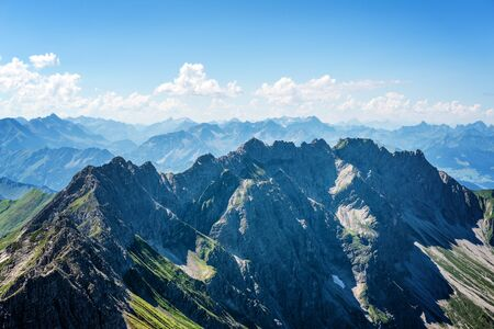 High altitude view on German alps with sharp peaks and partly cloudy sky with copy space above Stock Photo