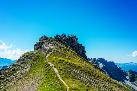 allgau: Path leading up to top of little mountain facing the Alps under blue sky in Allgau Germany