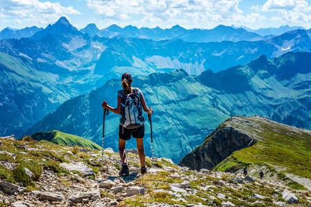 Several mountain ranges loom ahead for lone hiker as she stands at summit of one rocky overlook Stock Photo