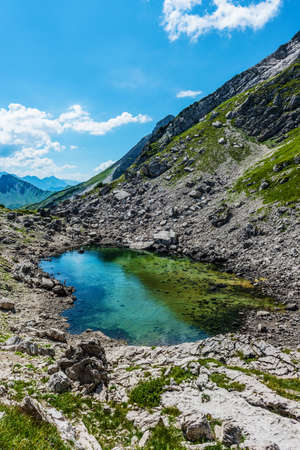 Scenic view of natural clear pool of water atop mountain with other tall ranges in the distance