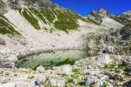 allgau: Green and rocky side of mountain with tiny Koblatsee lake located in the southern tip of Germany