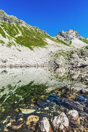 allgau: Old rocks and grassy hillside on mountain in the German Alps near Allgau under blue sky