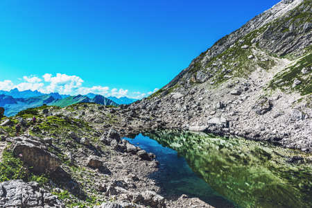 allgau: Reflective pool of water near rocky mountain summit during the summer in Allgau, Germany, Europe