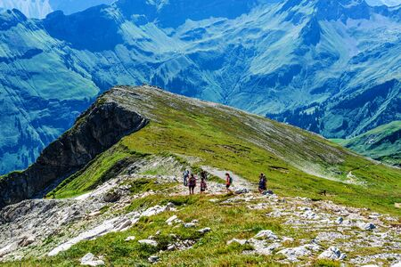 allgau: Group of backpackers hiking on Grosser Daumen in the Allgau Alps, Germany amidst spectacular mountain peaks and alpine scenery Stock Photo
