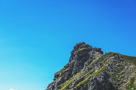 low angle view: Extreme low angle view of rocky mountain top under a clear blue sky on a pleasant afternoon