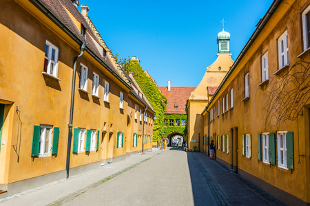 Augsburg, Germany - September 08, 2016: Narrow street between deep yellow walls of the historical low income housing in Germany known as the Fuggerei apartments