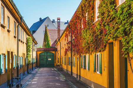 Augsburg, Germany - September 08, 2016: Colourful yellow buildings in Fuggerei, Augsburg, Germany lining a central courtyard, one of the oldest social housing complexes in the world