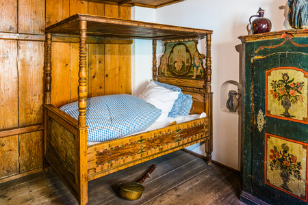 four poster bed: Augsburg, Germany - September 08, 2016: Historic architecture display of restored medieval era luxury bed in room with warming pot in the Fuggerei, Augsburg, Germany