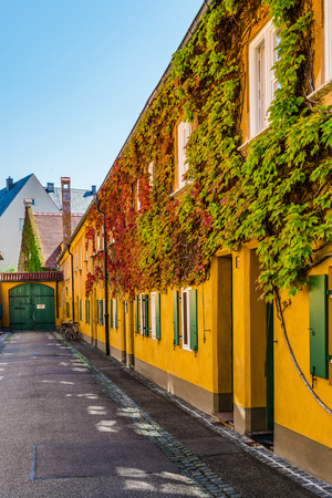 Augsburg, Germany - September 08, 2016: Colorful bright yellow creeper covered facade of an apartment block in Fuggerei, Augsburg, the oldest social housing in the world Editorial