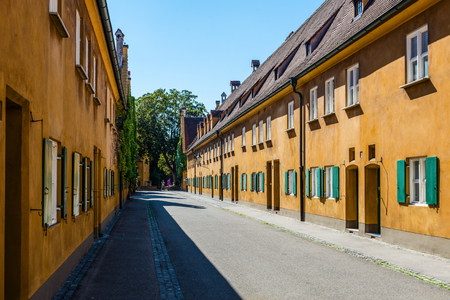 Augsburg, Germany - September 08, 2016: Street of colorful yellow old buildings used as the first form of social housing in Fuggerei, Augsburg, Bavaria, Germany Editorial