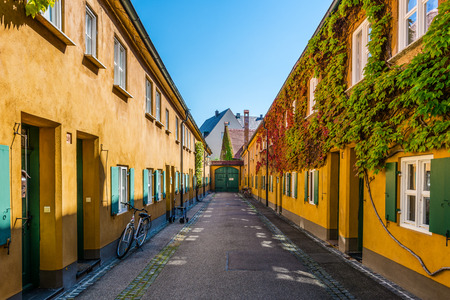 yellow walls: Facing walls in yellow paint and green window shutters at the Fuggerei houses in Germany