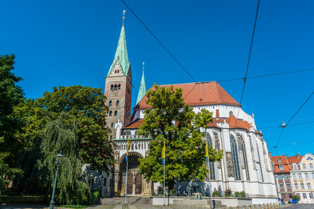 romance sky: Exterior facade of the Gothic Augsburg Cathedral, Bavaria, Germany against a sunny blue sky in a travel and tourism concept