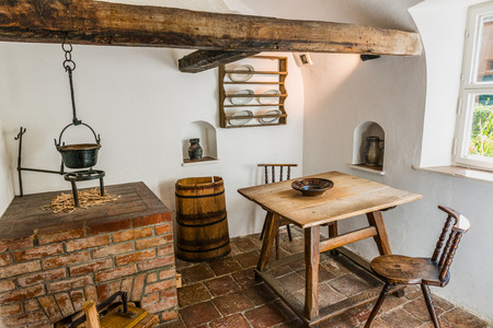 table and chairs: Augsburg, Germany - September 08, 2016: Historical display of medieval kitchen with table, chair, stove and stone block floor in the Fuggerei, Augsburg, Germany Editorial