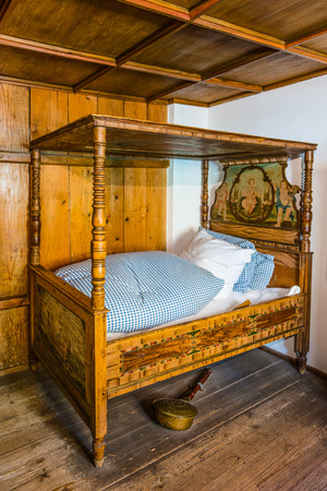 Augsburg, Germany - September 08, 2016: Restored medieval era bed with warming pot on display for tourists in the Fuggerei, Augsburg, Germany Editorial