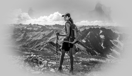 wanderlust: Grayscale portrait of smiling female hiker in hat and holding poles with vignette border