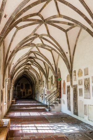 Augsburg, Germany - September 08, 2016: Old vaulted Gothic passage in the crypt of the historical Augsburg Cathedral, Bavaria, Germany with wall frescoes and plaques lit by daylight from the windows