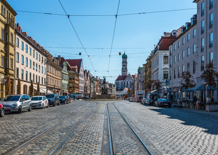 recedes: Augsburg, Germany - September 08, 2016: Tram lines in Maximilian Street, Augsburg, Bavaria, Germany with a view along the cobbled street lined with historic architecture and parked cars