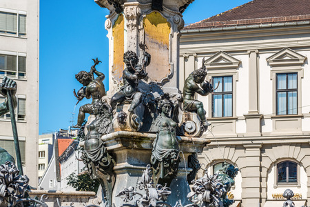 Bronze fountains with cherubs at the foot of the statue of the Emperor Augustus, Augsburg, Bavaria, Germany